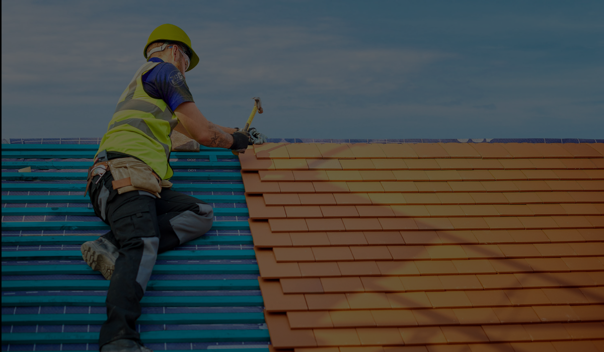 construction worker on roof hammering tiles