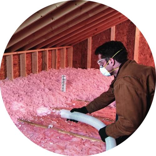 man installing insulation in attic